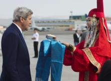A woman in traditional attire presents U.S. Secretary of State John Kerry with cheese curds as he disembarks from his plane upon arrival at Chinggis Khaan International Airport in Ulaanbaatar, Mongolia, June 5, 2016. REUTERS/Saul Loeb/Pool.